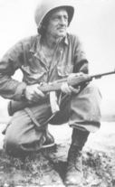 Soldier with rifle, kneeling in field during Korean War.