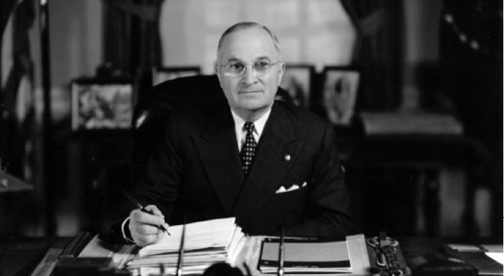 President Truman signing documents on desk